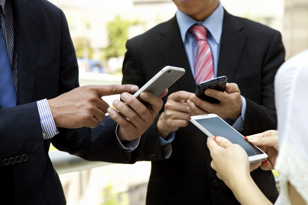 Businesspeople sharing information using phones
