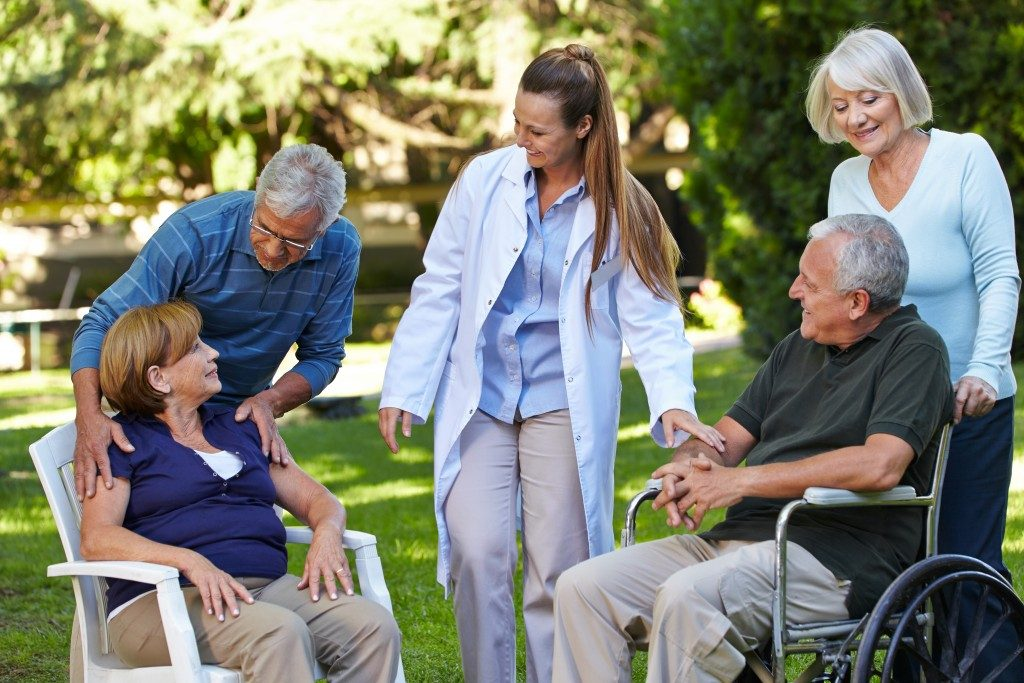 Seniors relaxing in the park with a nurse