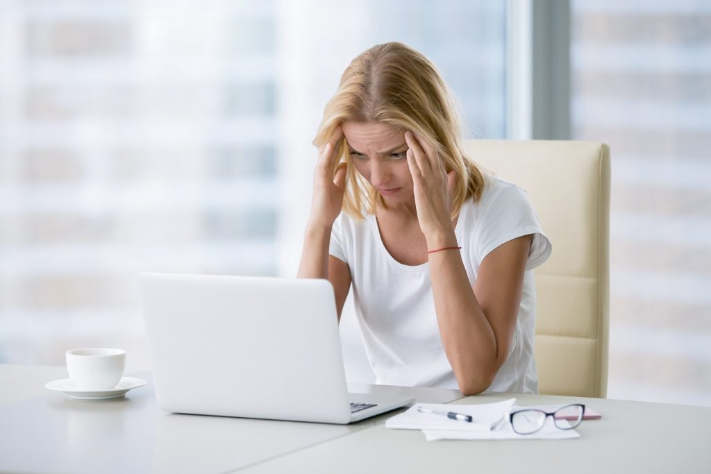 Stressed employee looking at her laptop
