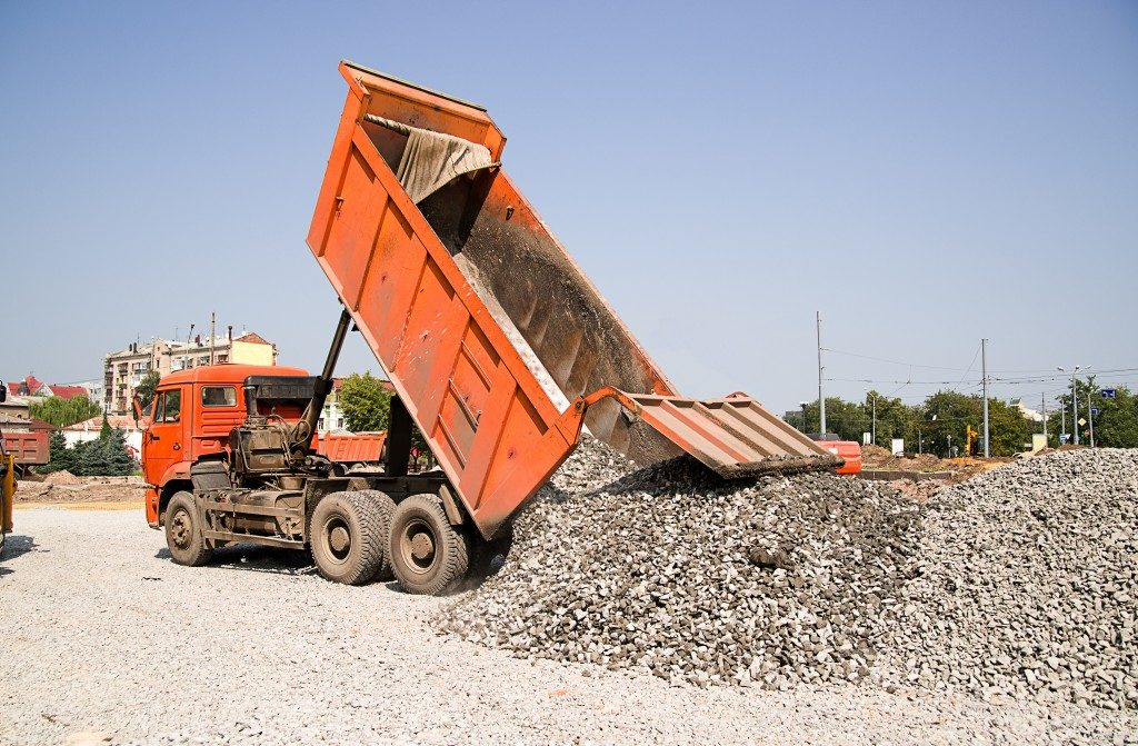 The truck pours the crushed rocks on the road construction