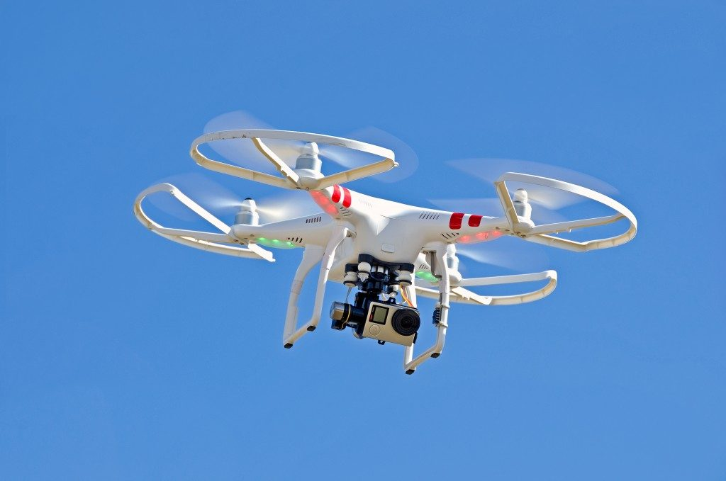 white drone with camera hovering in a bright blue sky