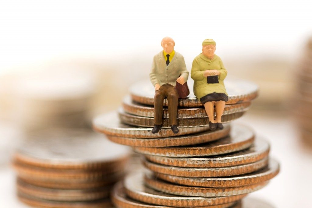 two figures of seniors sitting on coins
