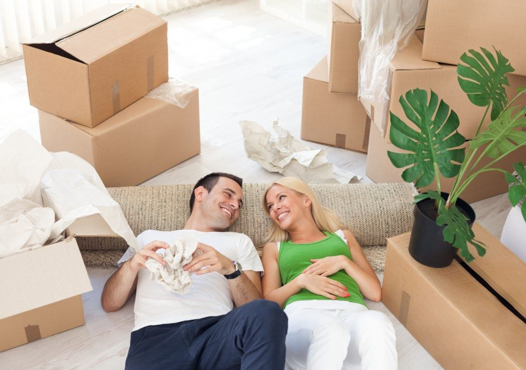 Young smiling couple relaxing in the middle of cardboard boxes